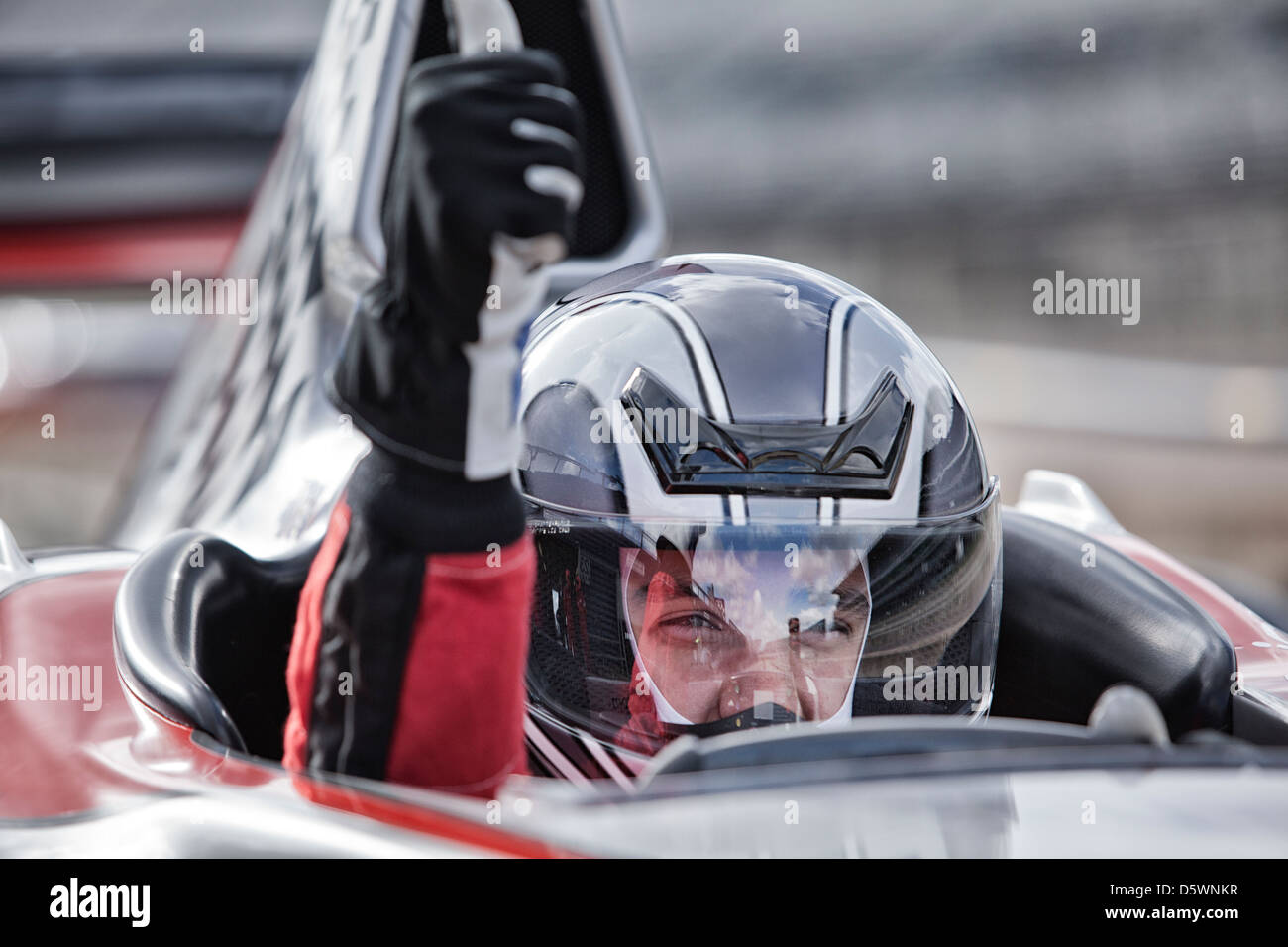 Racer giving thumbs up from car on track - Stock Image