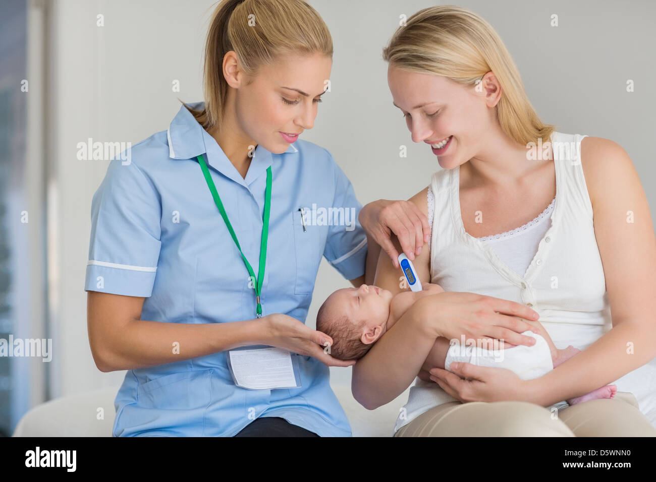 Mother and nurse taking newborn baby's temperature - Stock Image