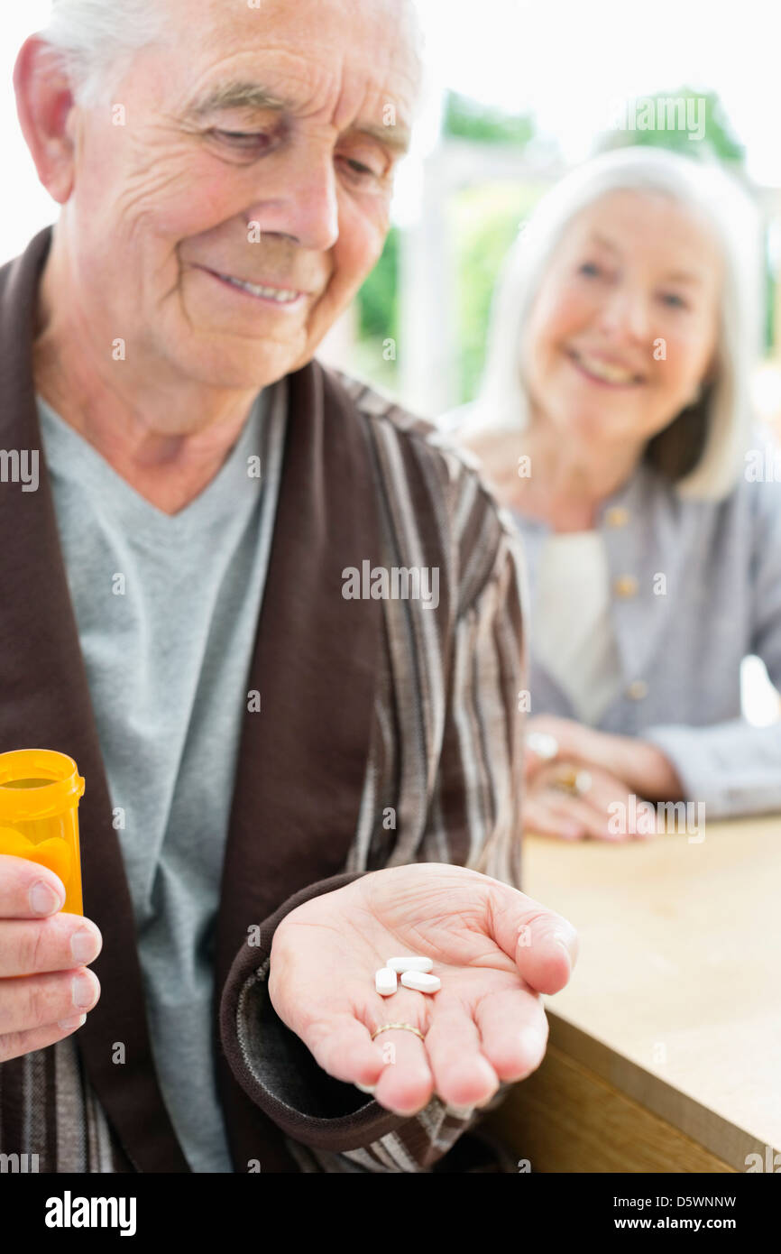 Older man with handful of pills - Stock Image