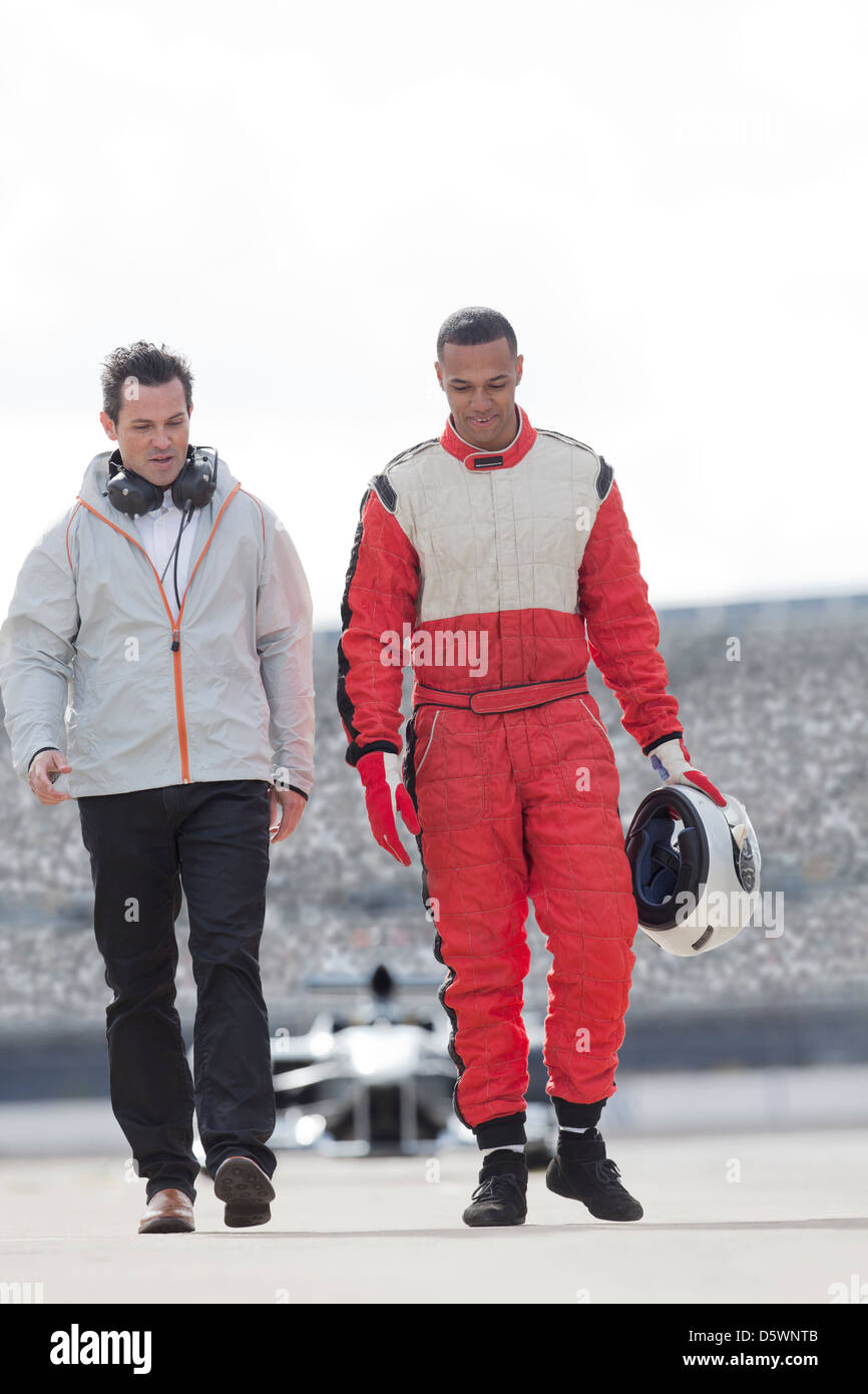 Racer and manager walking on track - Stock Image