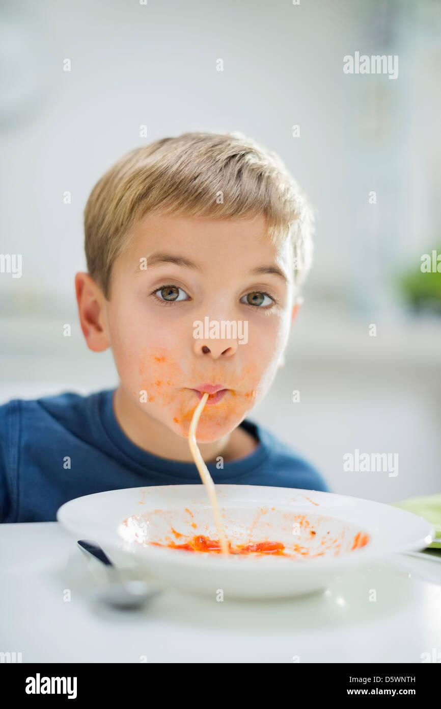 Boy slurping spaghetti at table - Stock Image