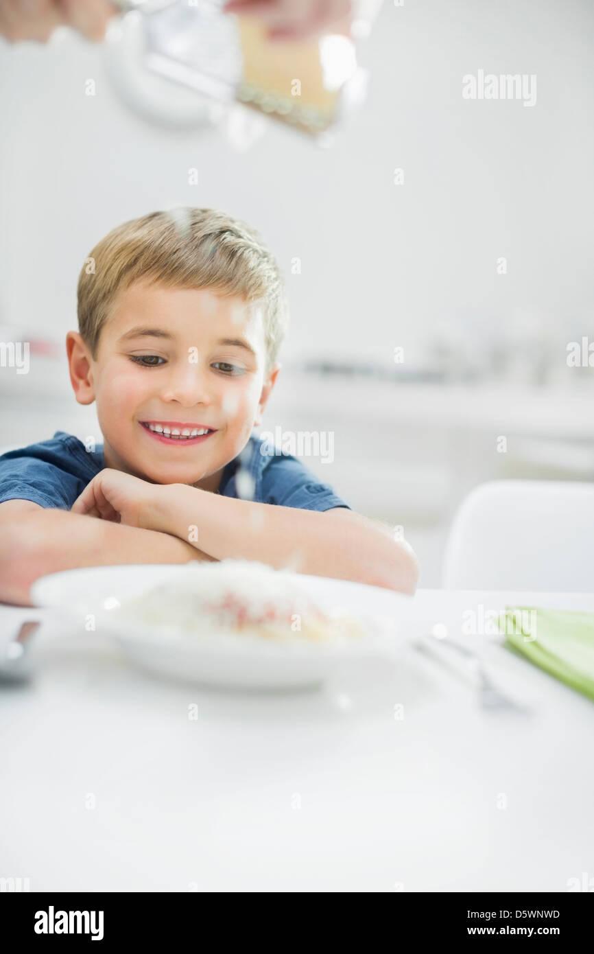 Smiling boy having spaghetti at table Stock Photo