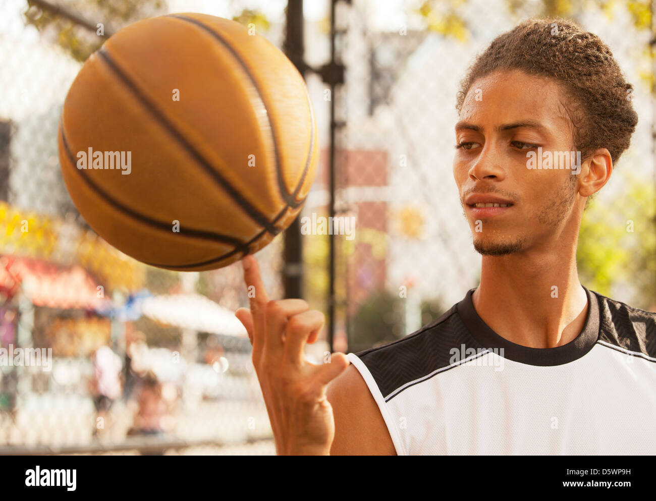 Man spinning basketball on finger - Stock Image