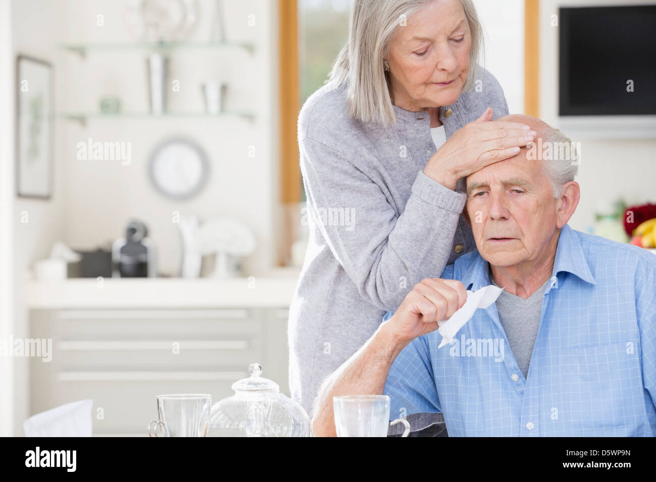 Older woman feeling sick husband's forehead - Stock Image