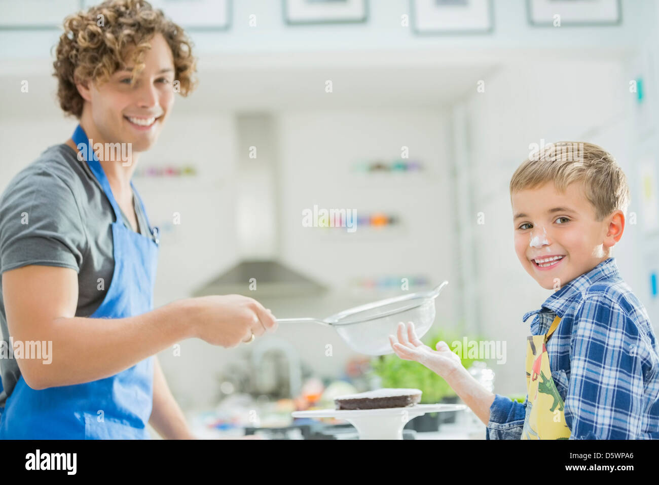 Father and son baking in kitchen - Stock Image
