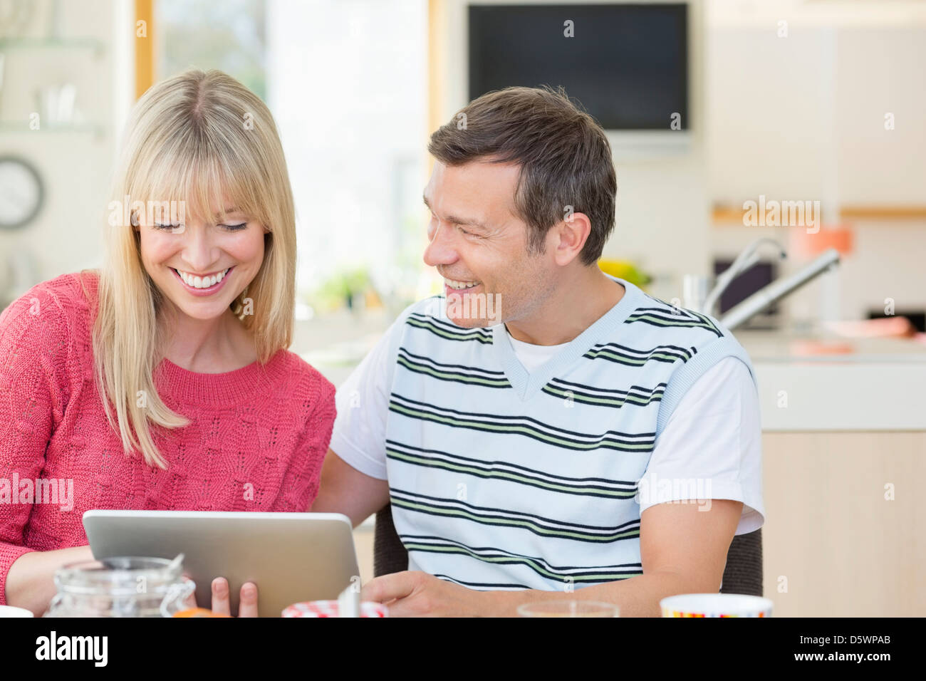 Couple using tablet computer at table - Stock Image