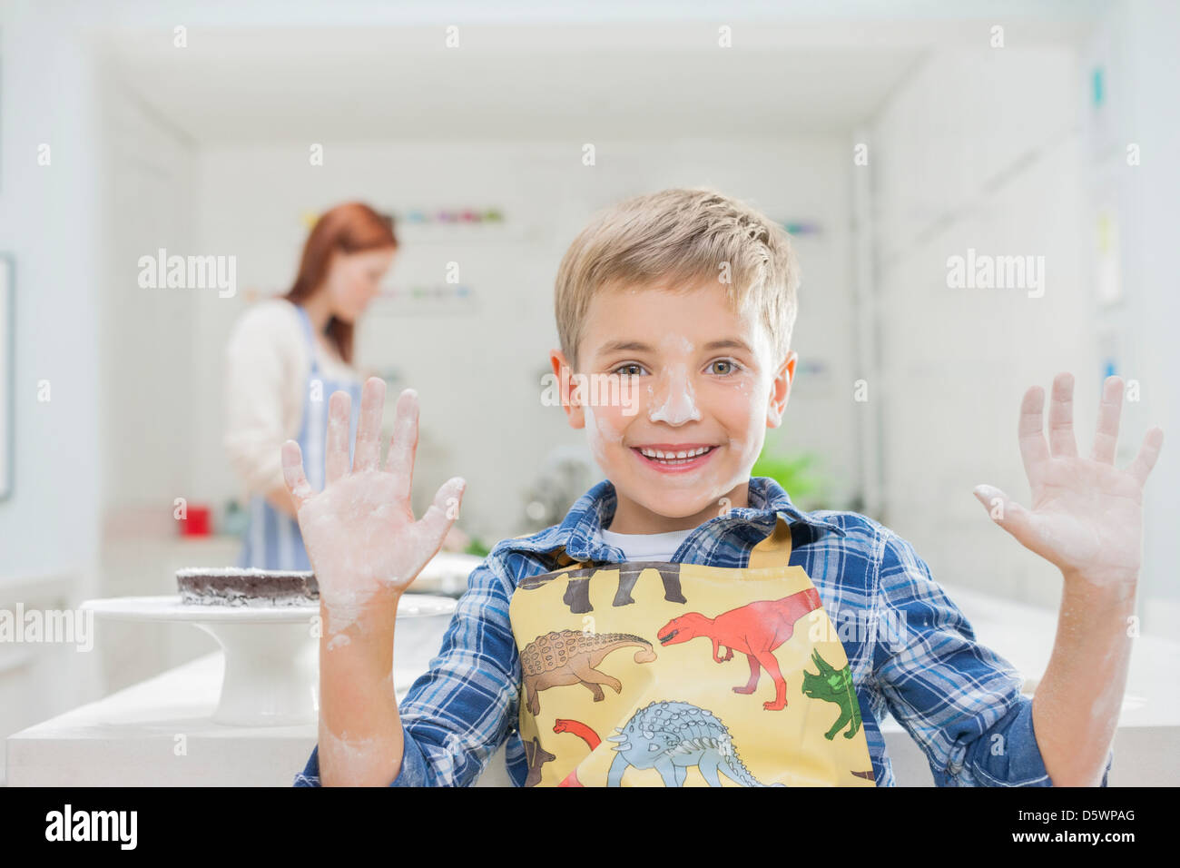 Boy covered in flour in kitchen - Stock Image