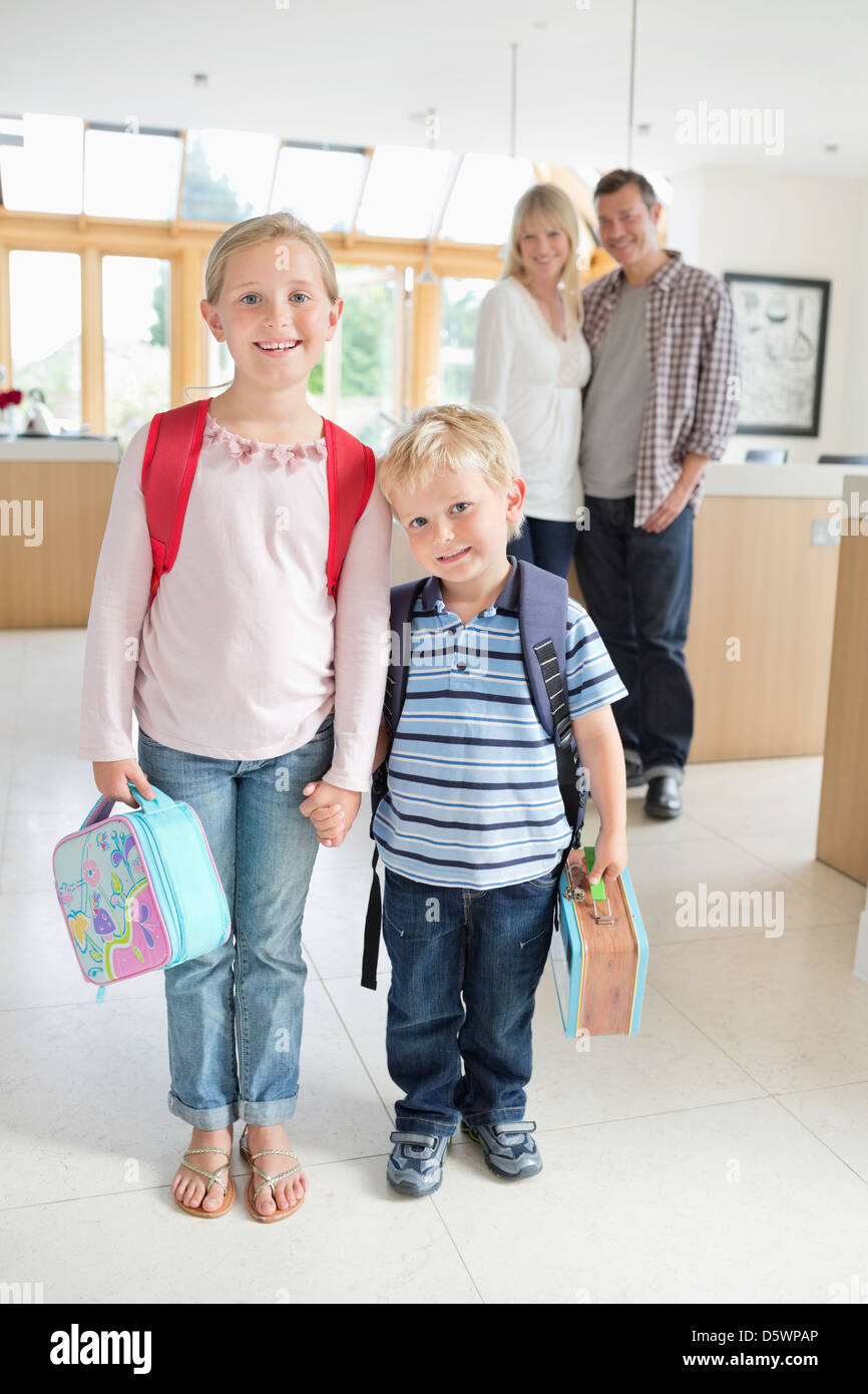 Children ready for school in kitchen - Stock Image