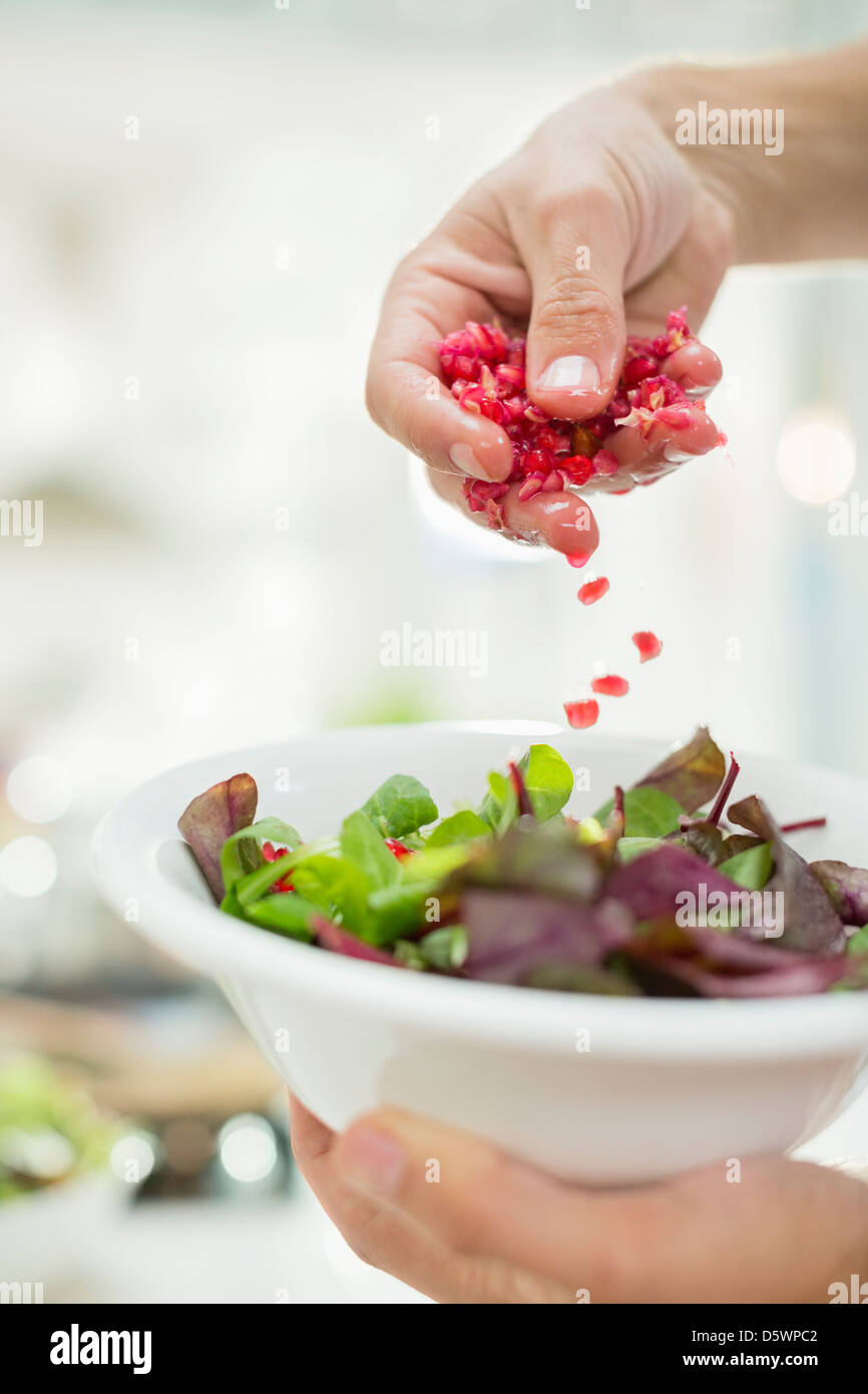 Woman making salad in kitchen Stock Photo