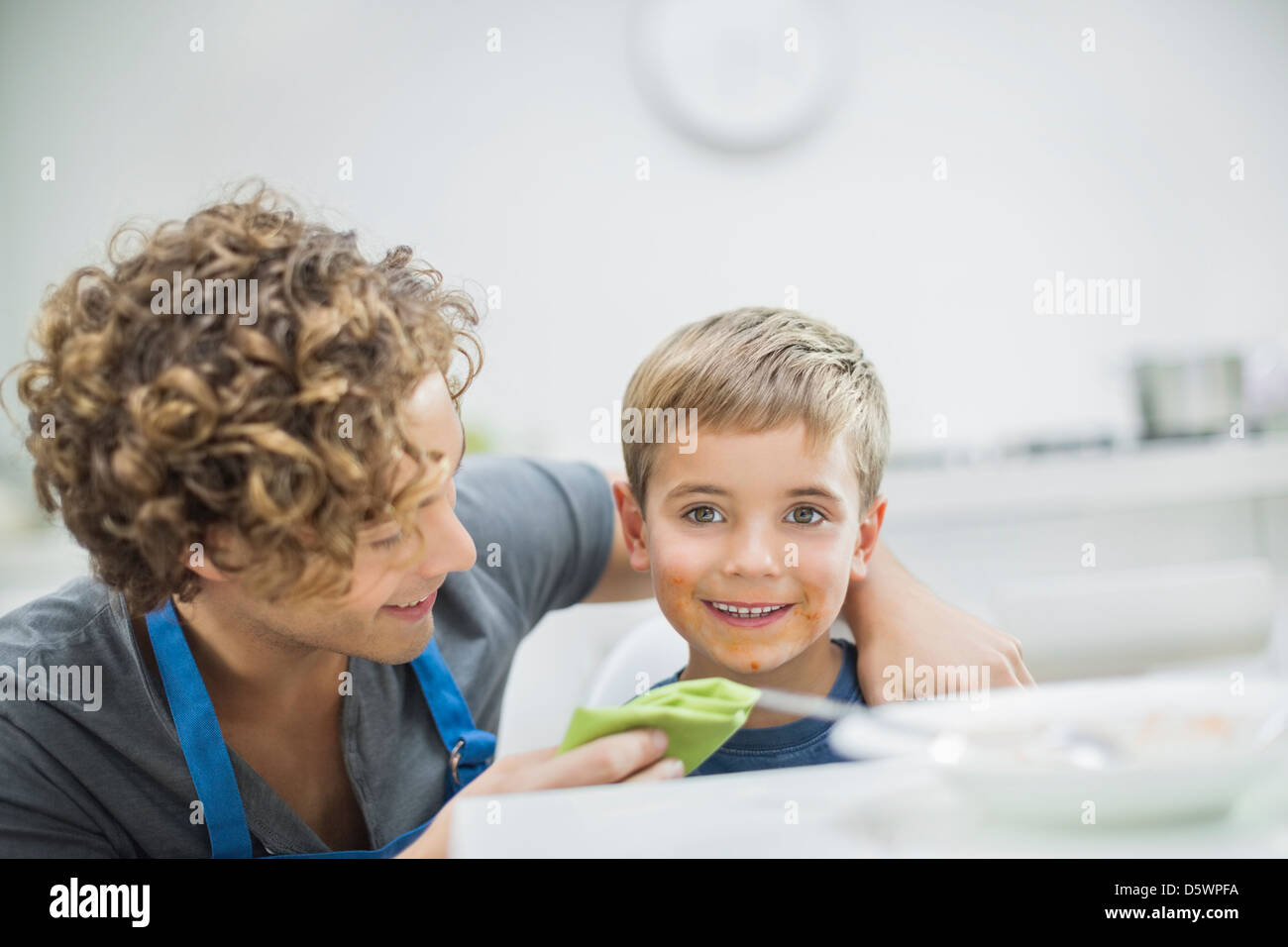 Father wiping son's mouth at table - Stock Image