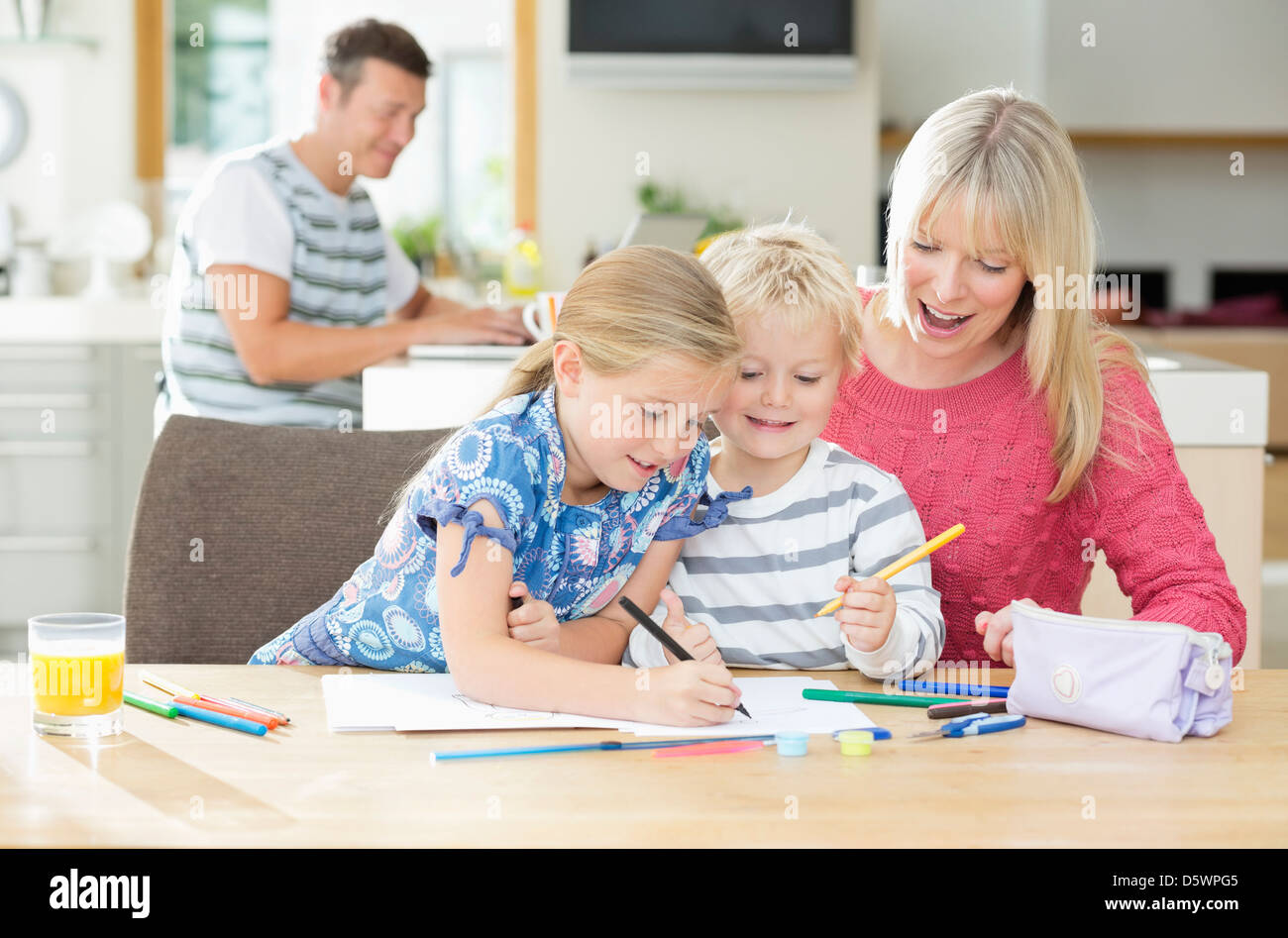 Mother and children coloring at table Stock Photo