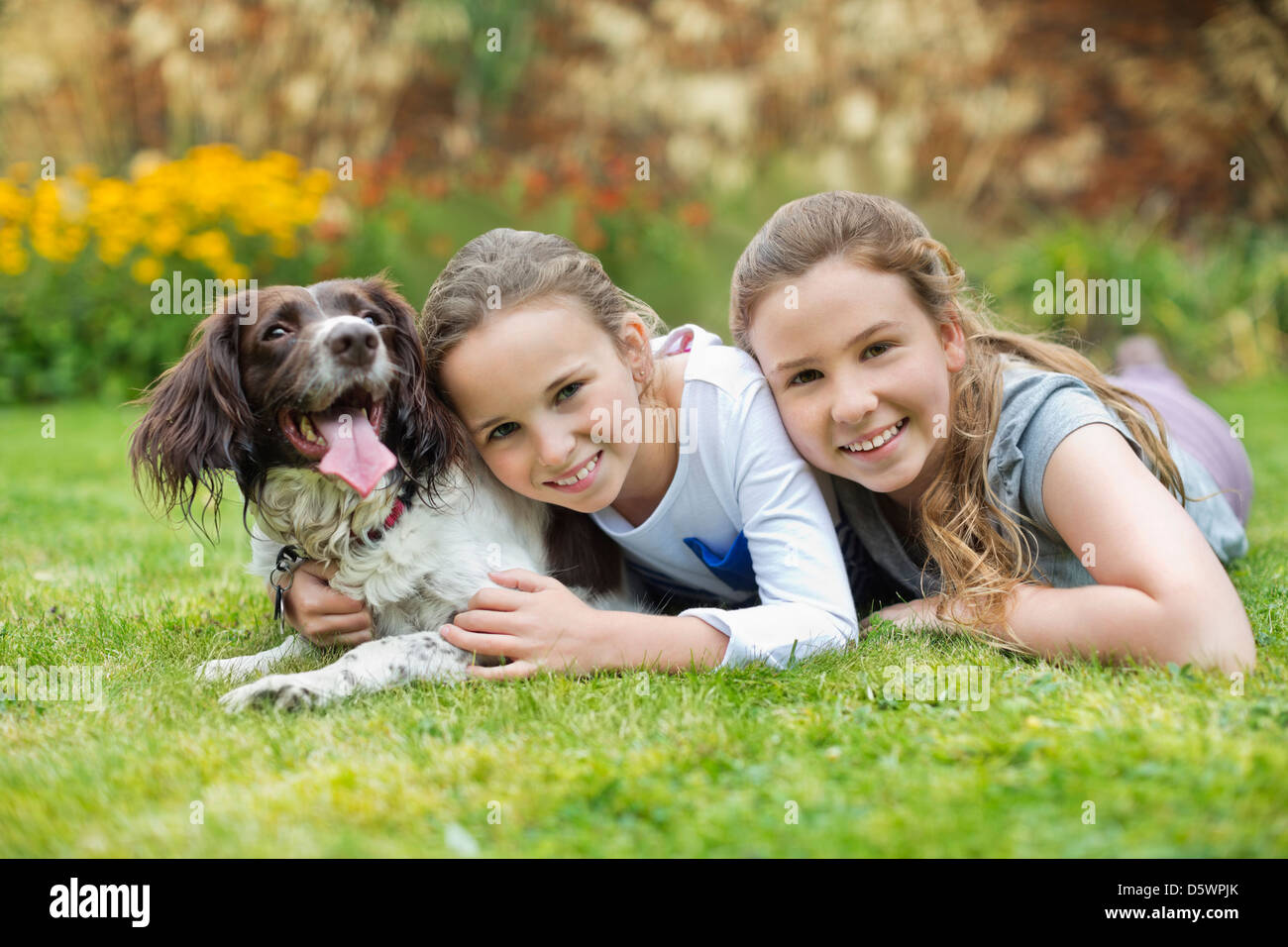 Smiling girls relaxing with dog on lawn Stock Photo