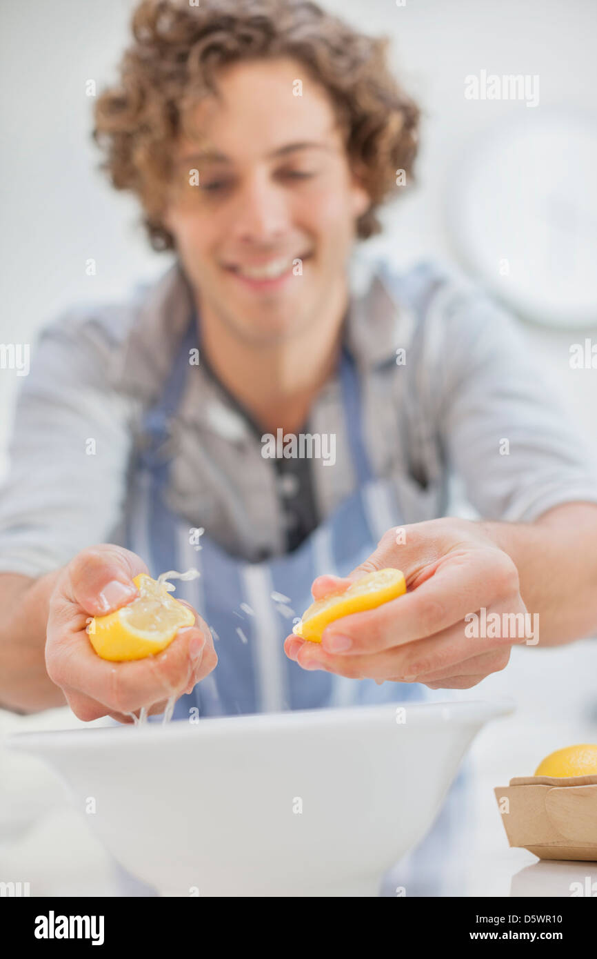 Man squeezing lemons in kitchen - Stock Image
