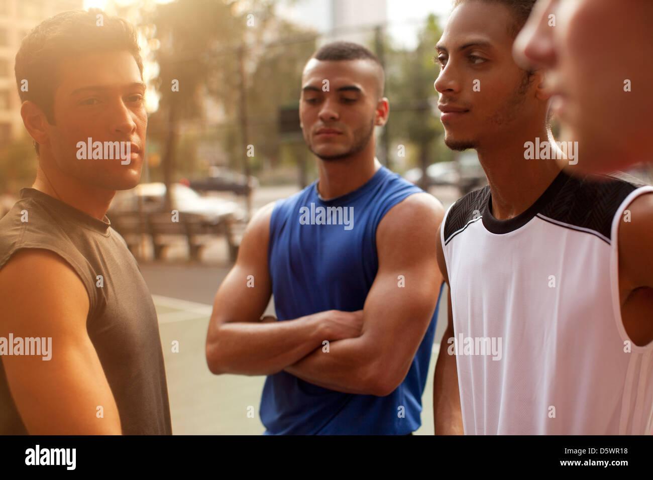 Men standing on basketball court - Stock Image
