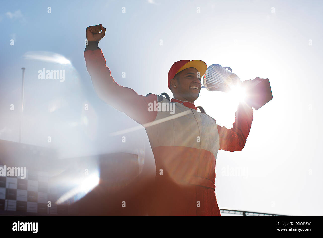Cheering racer holding trophy on track Stock Photo