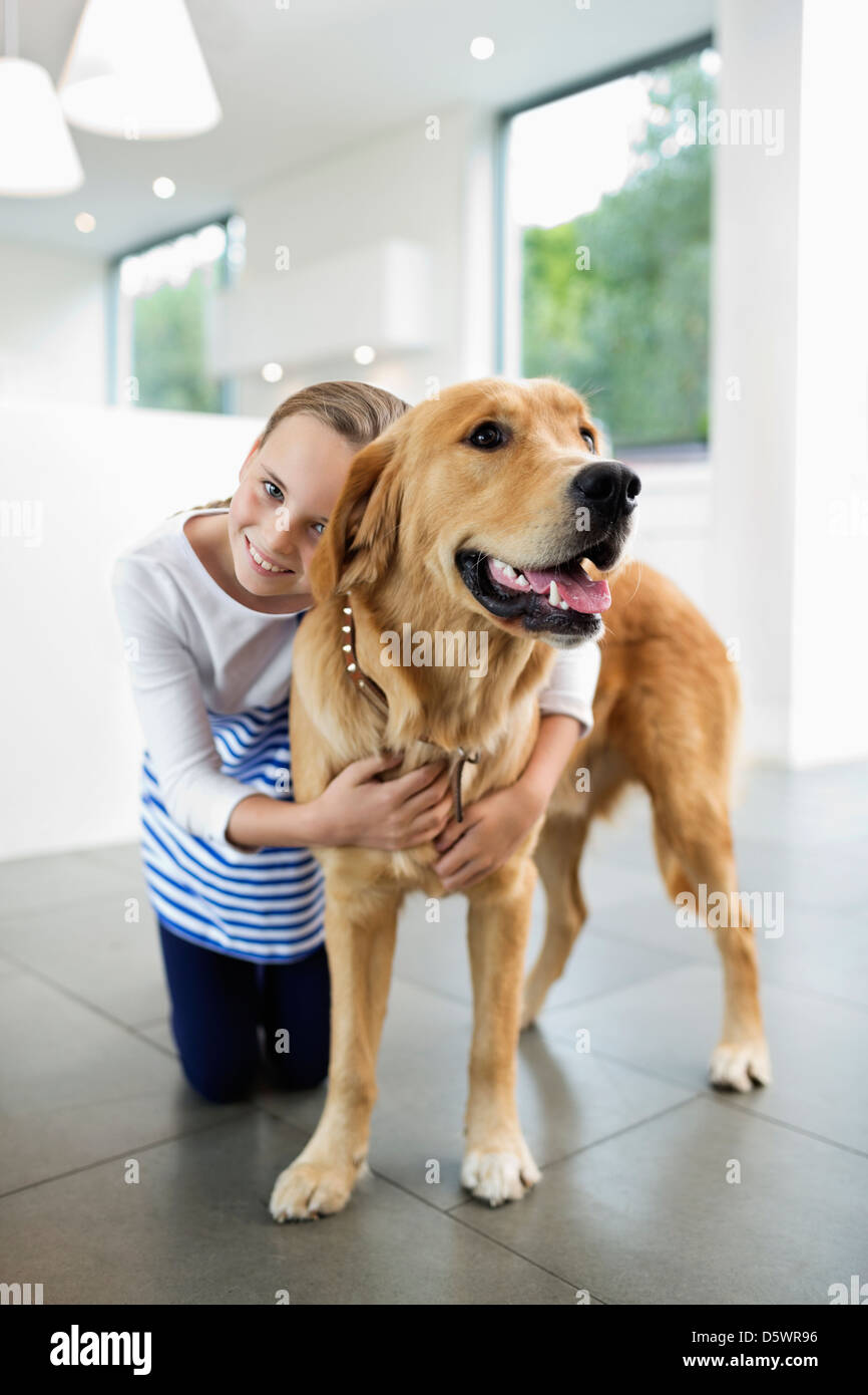 Girl hugging dog indoors Stock Photo