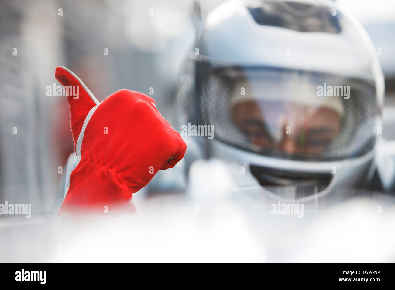 Racer giving thumbs up in car - Stock Image