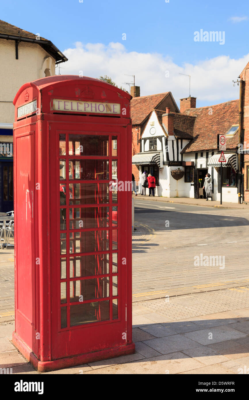 Traditional red public telephone box kiosk (K6) on a street in Stratford-upon-Avon, Warwickshire, England, UK, Britain - Stock Image