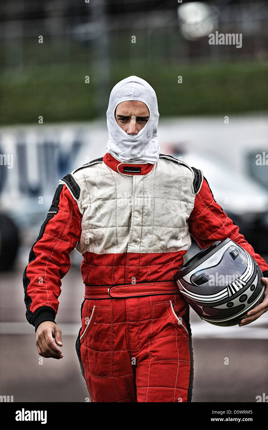 Racer carrying helmet on track - Stock Image