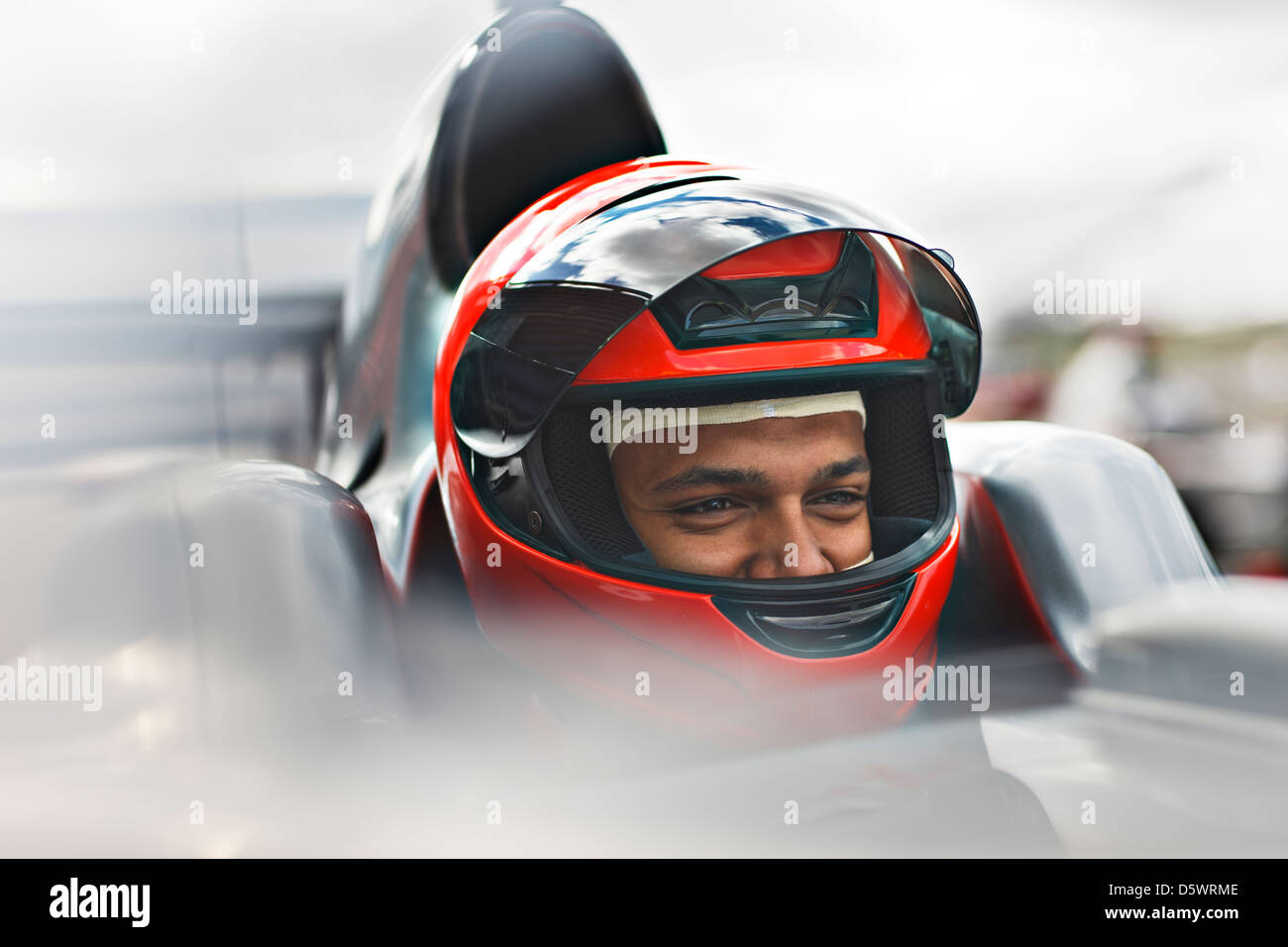Racer sitting in car on track - Stock Image