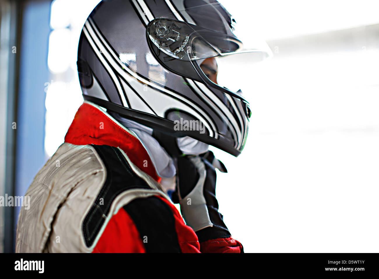 Racer tying on helmet in garage - Stock Image