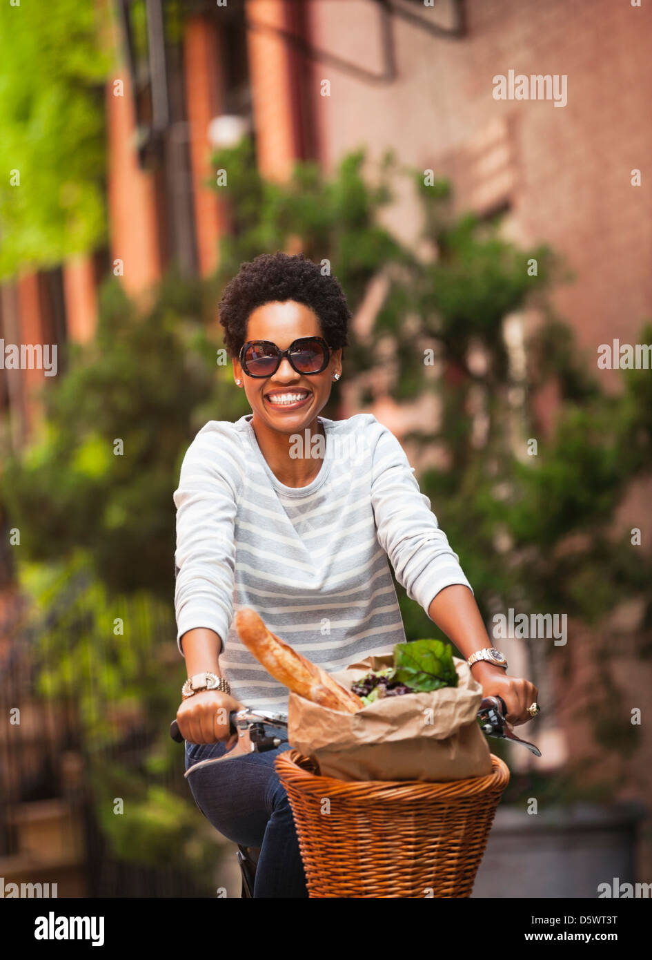 Woman riding bicycle on city street - Stock Image