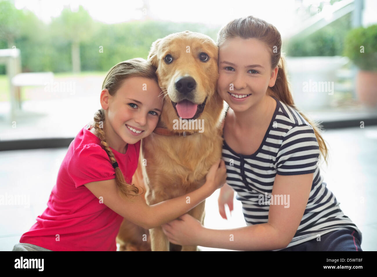 Smiling girls hugging dog indoors Stock Photo