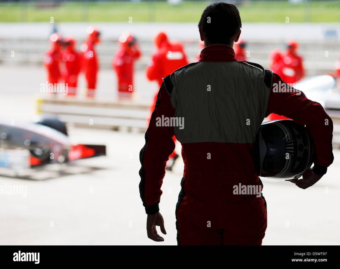 Racer carrying helmet on sidelines - Stock Image