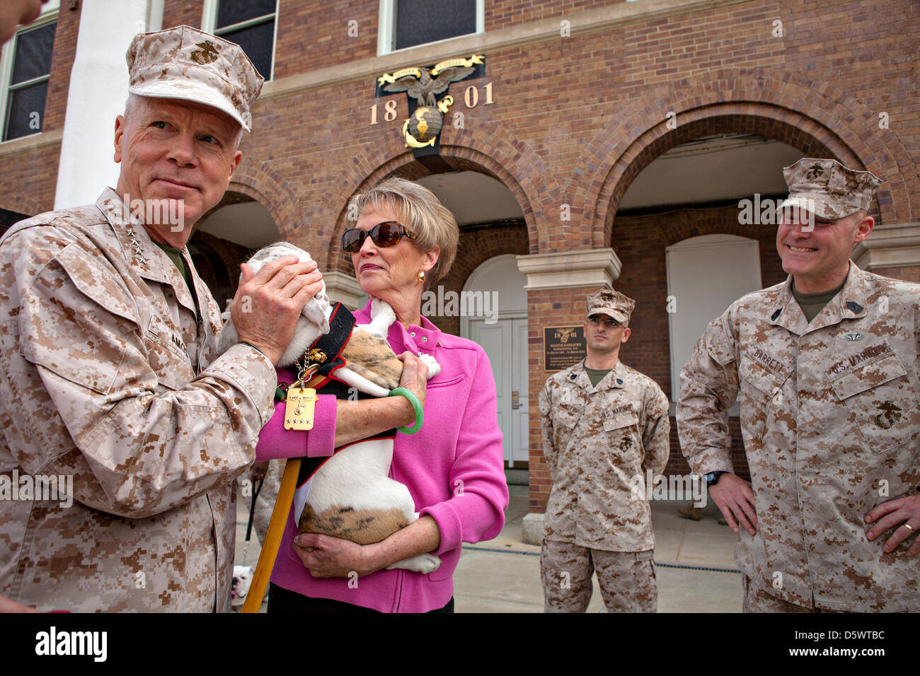 Commandant of the Marine Corps Gen. James F. Amos and his wife Bonnie embrace Pfc Chesty XIV, official mascot of Stock Photo