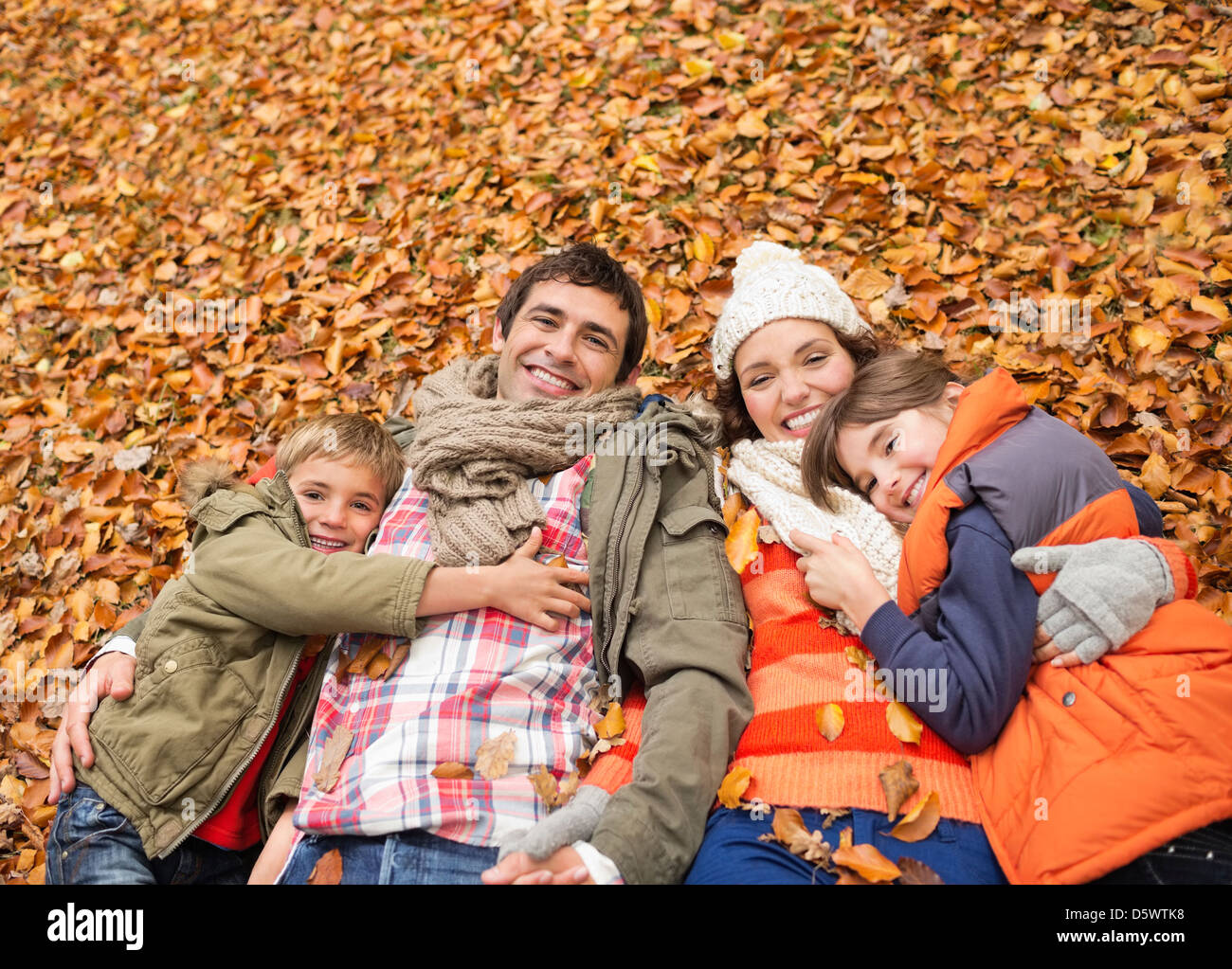 Smiling family laying in autumn leaves - Stock Image