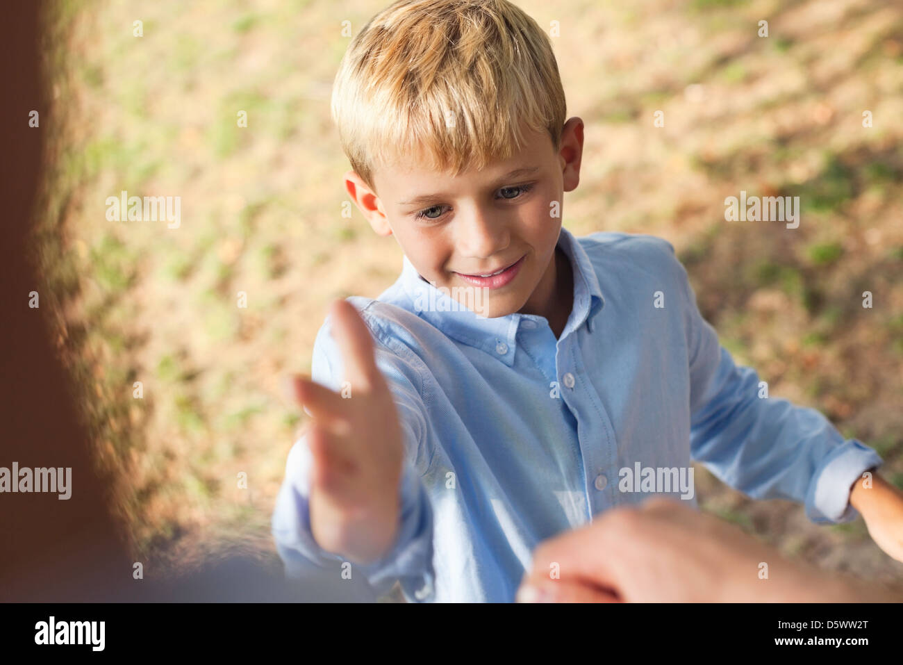 Father and son high fiving outdoors - Stock Image