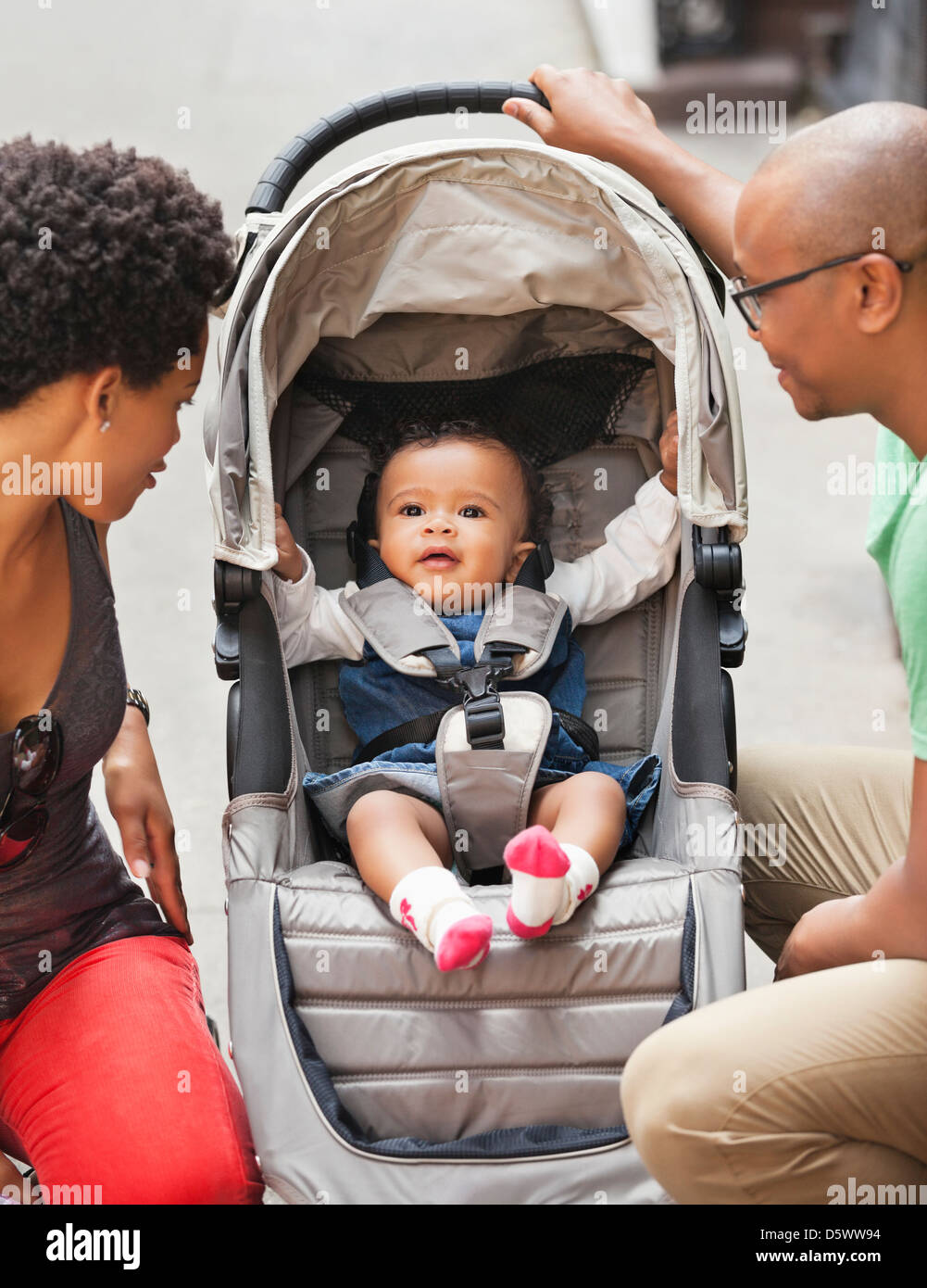 Parents with baby in stroller on city street - Stock Image
