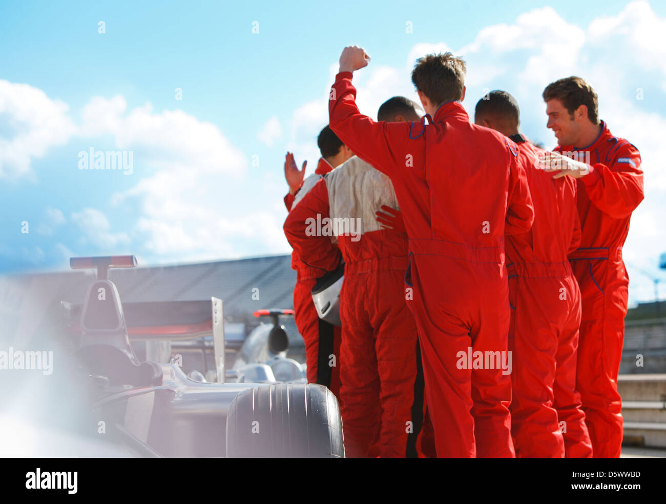 Racer and team cheering on track - Stock Image
