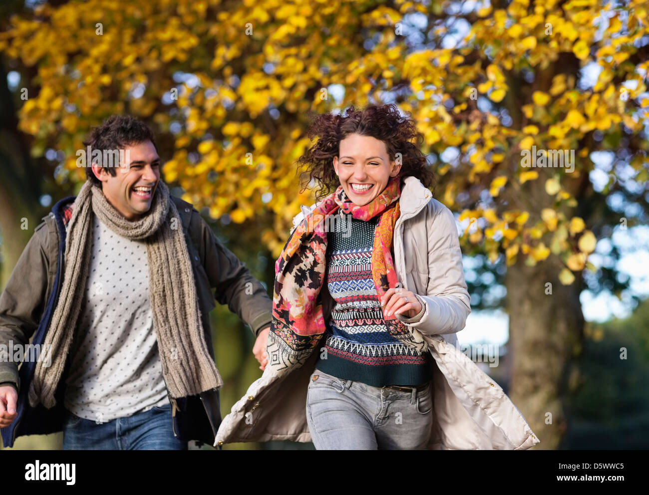 Couple running together in park - Stock Image