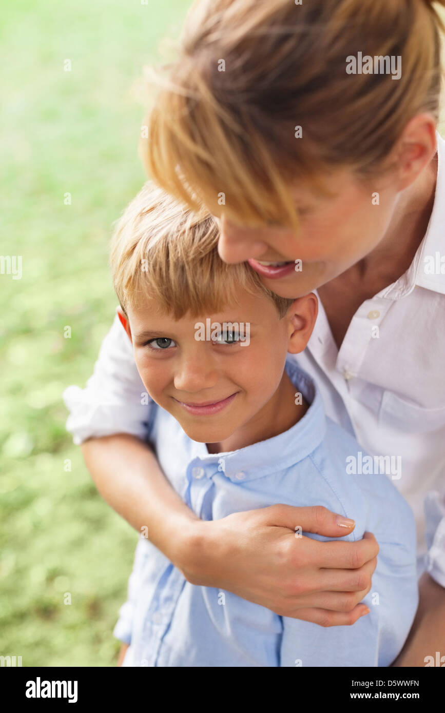 Mother hugging son in park - Stock Image