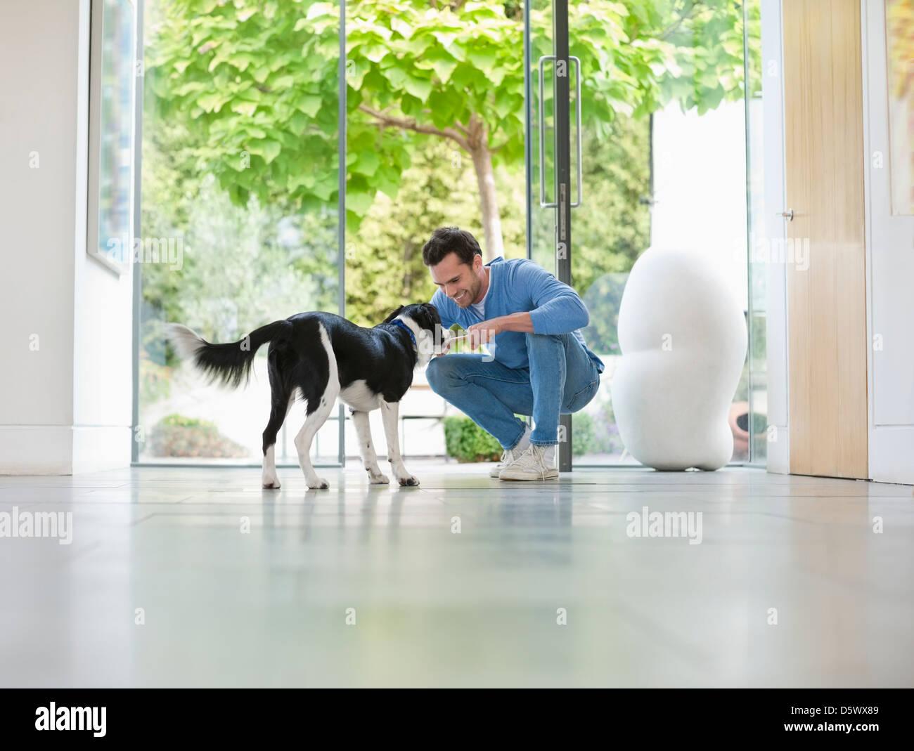 Smiling man petting dog in kitchen - Stock Image
