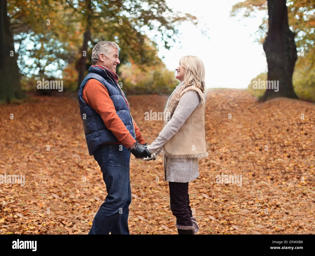 Older couple holding hands in park - Stock Image