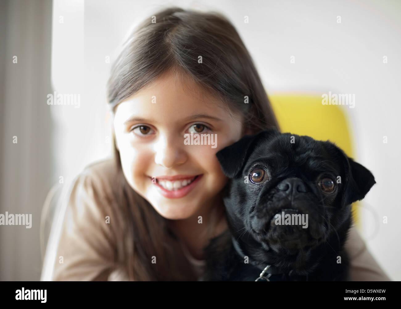 Smiling girl holding dog - Stock Image