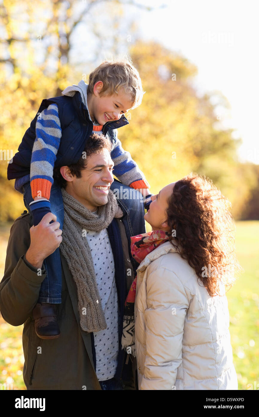 Family smiling together in park - Stock Image
