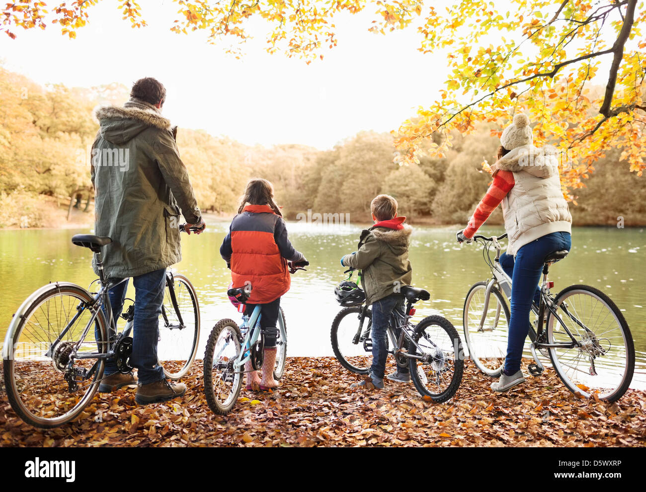 Family sitting on bicycles together in park - Stock Image