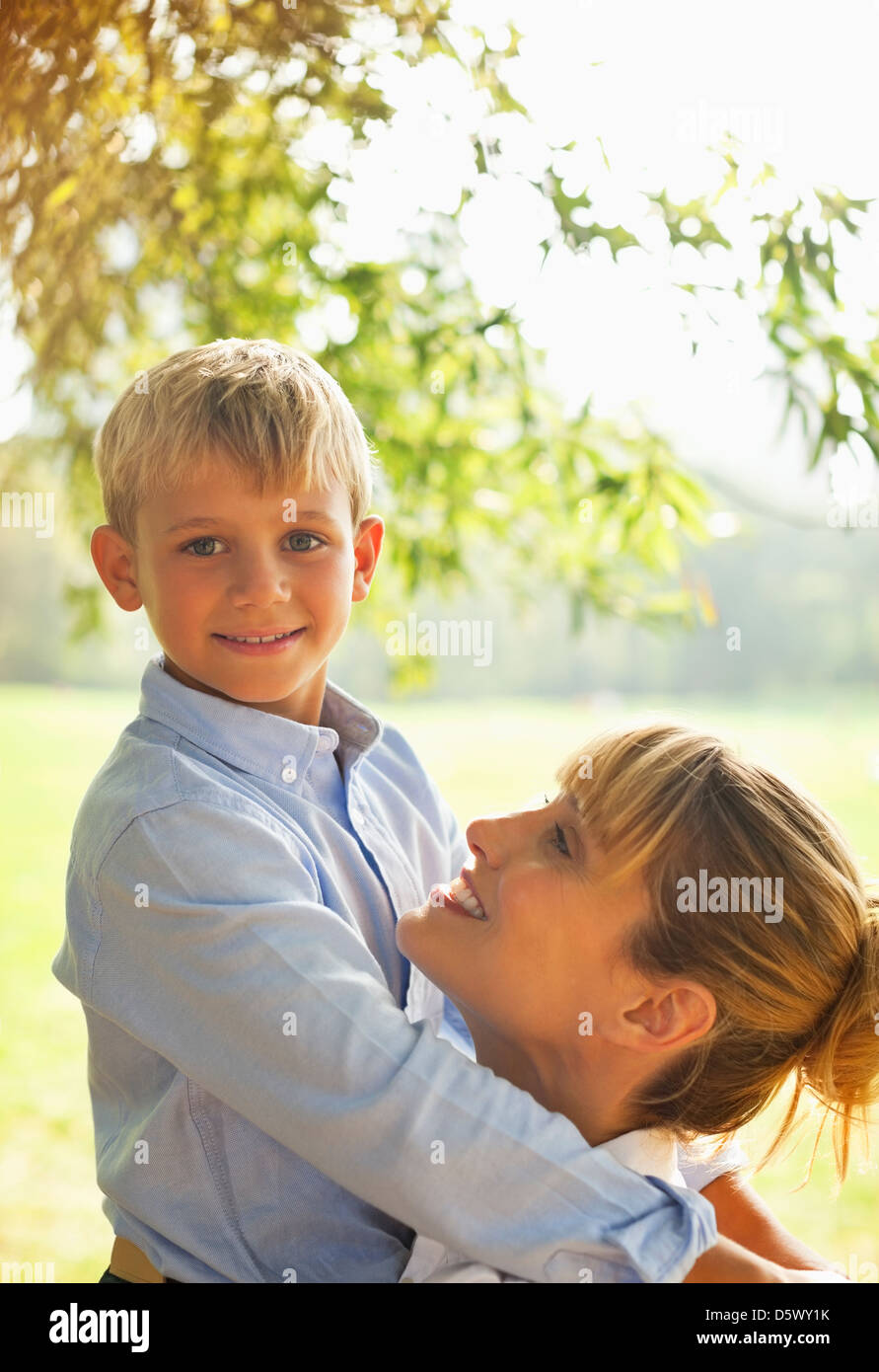 Mother and son hugging in park - Stock Image