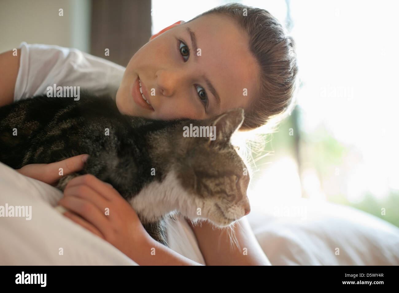 Girl petting cat on bed - Stock Image