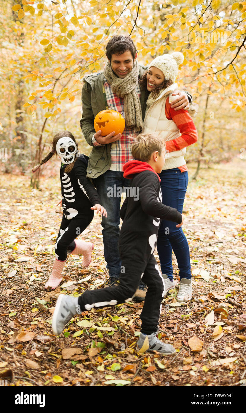 Couple with children in skeleton costumes in park - Stock Image