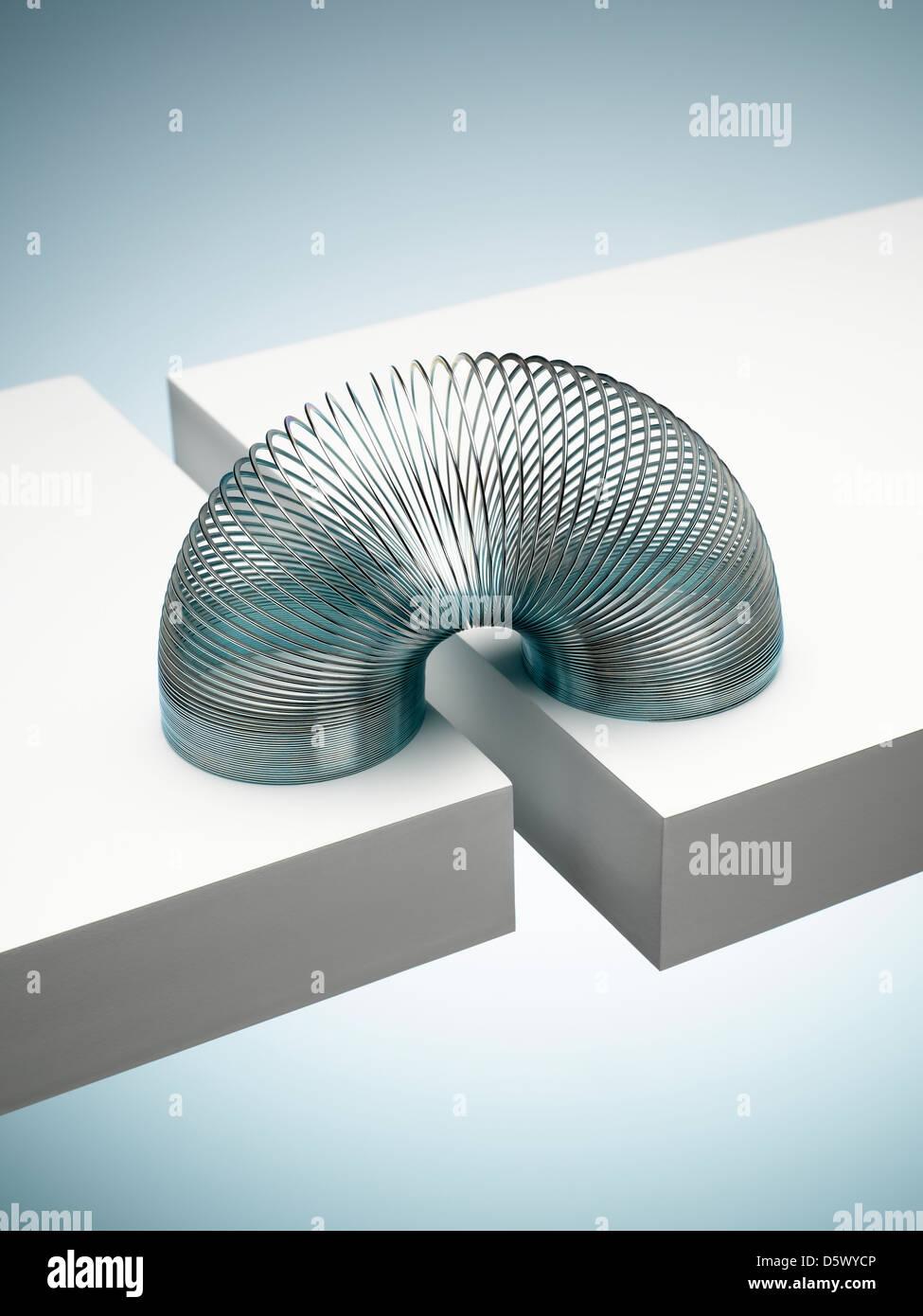 Metal slinky spanning space between blocks - Stock Image