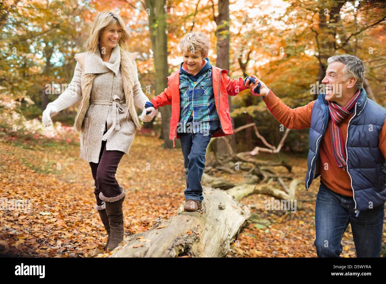 Family walking on log in park - Stock Image