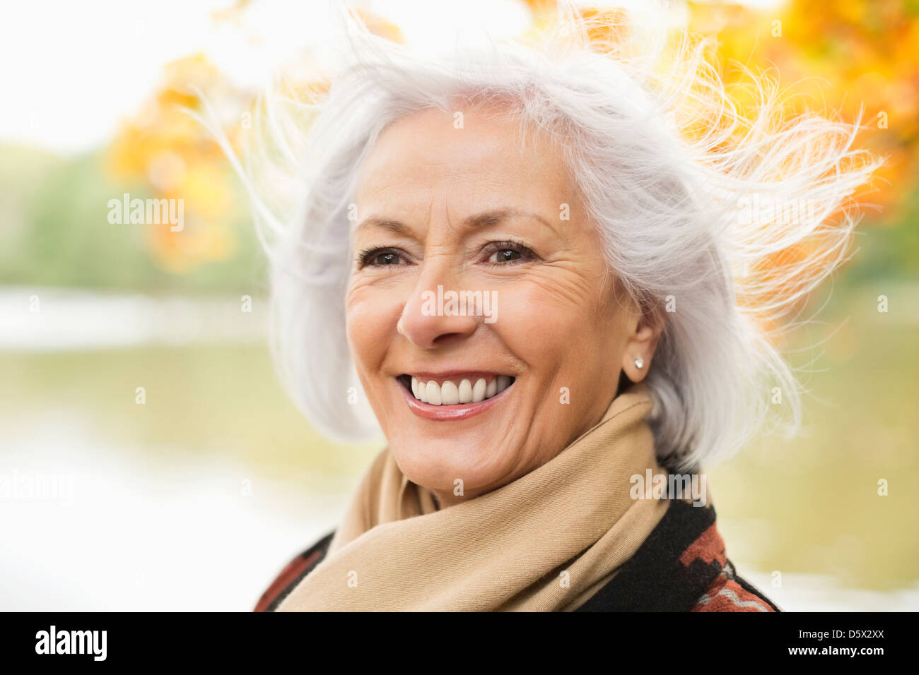 Smiling older woman standing in park - Stock Image