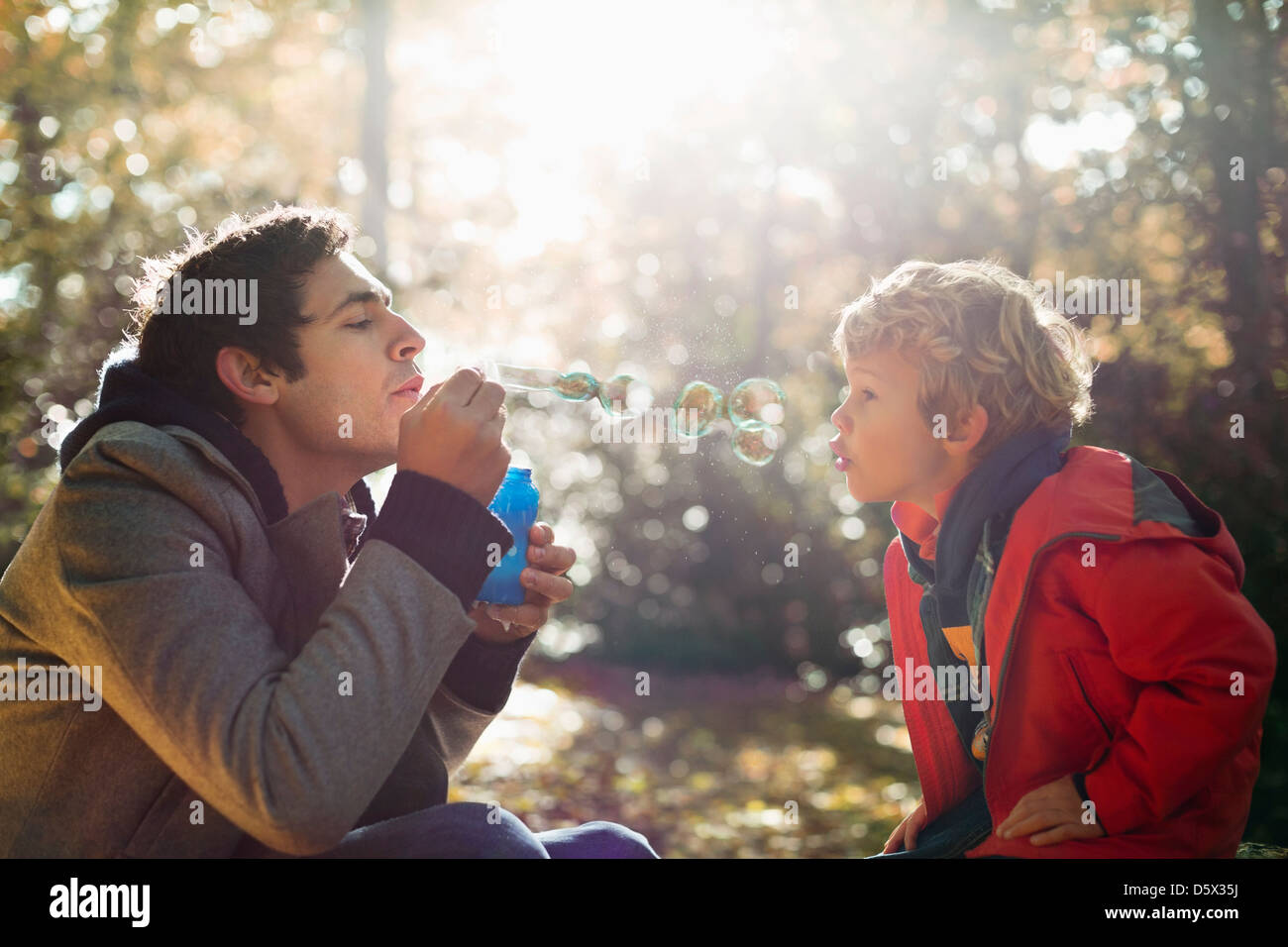 Father and son blowing bubbles in park - Stock Image