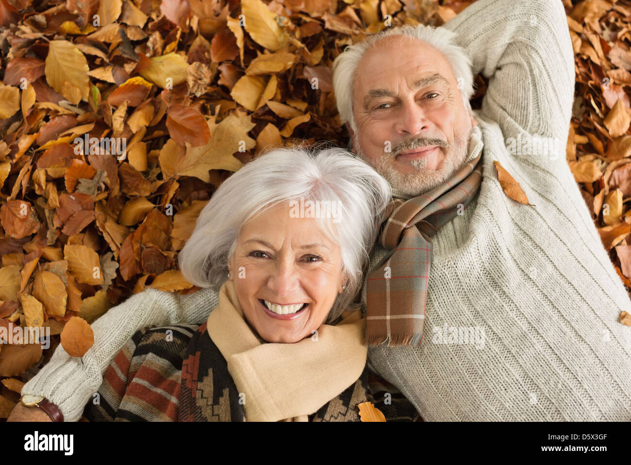 Older couple laying in autumn leaves - Stock Image