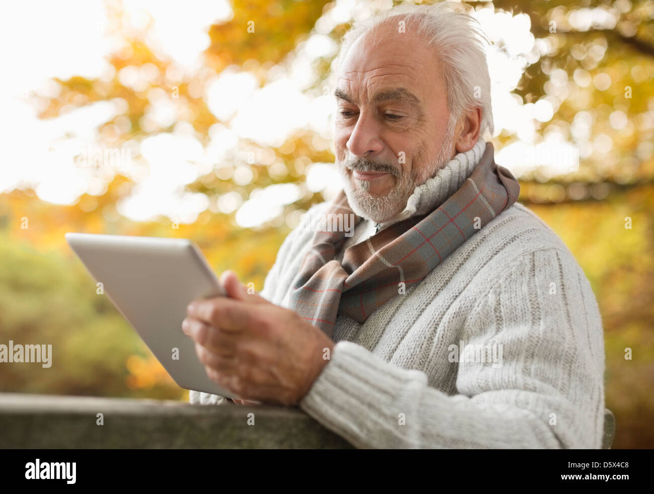 Older man using tablet computer in park - Stock Image