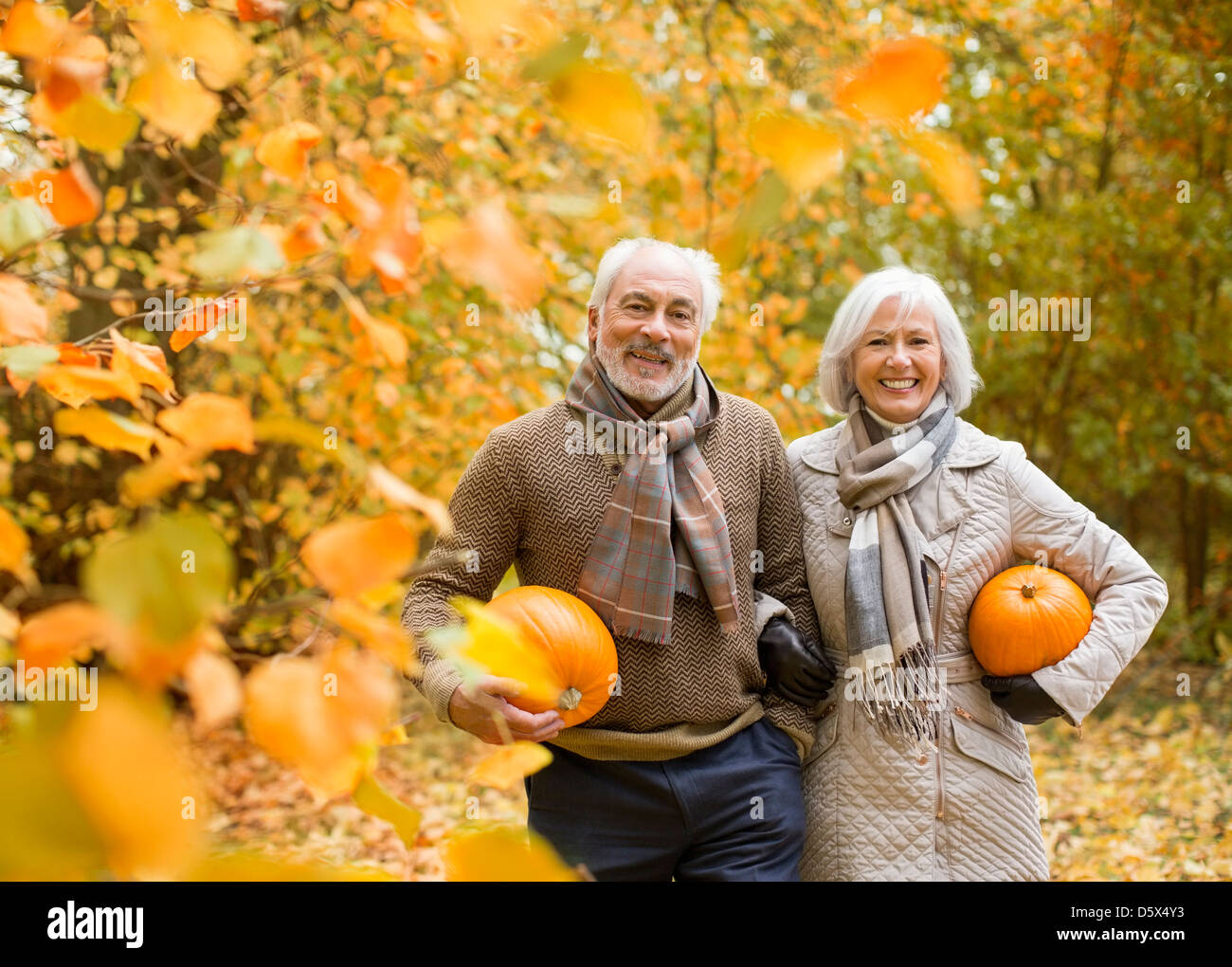 Older couple carrying pumpkins in park - Stock Image